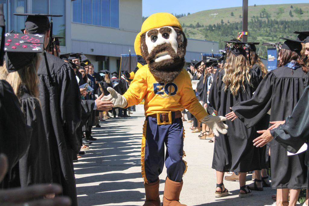 Students high fiving monty the mountaineer at spring commencement