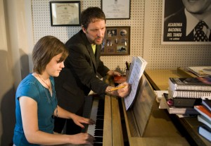A student sits at a piano, while Professor Matt Cooper marks her music with a pencil.