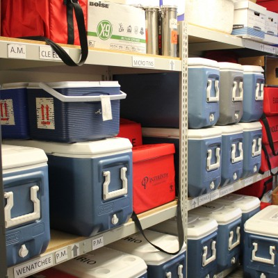 Racks of coolers are transported overnight by couriers serving clinics across the region.