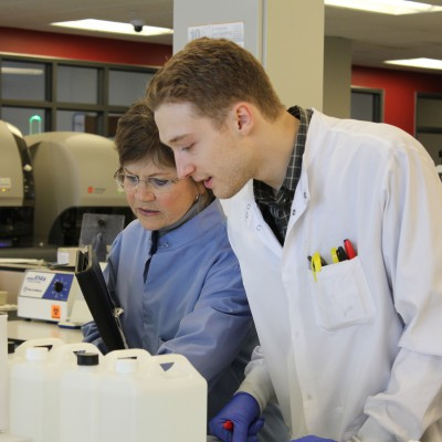 Judy Kennedy, '88, and Brian Mandella, '17, inspect a machine that measures chemiluminescence.