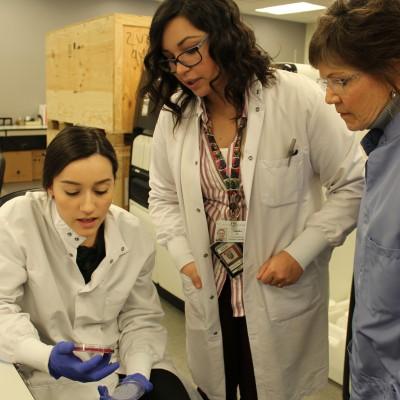Taran Goodwin shows Sashka Zungul, '12, and Judy Kennedy, '88, a petri dish growing samples from a patient.