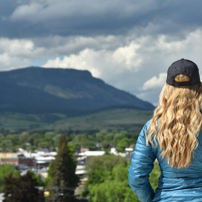 An EOU Student standing on campus looking out over La Grande with Mt. Emily in the distance