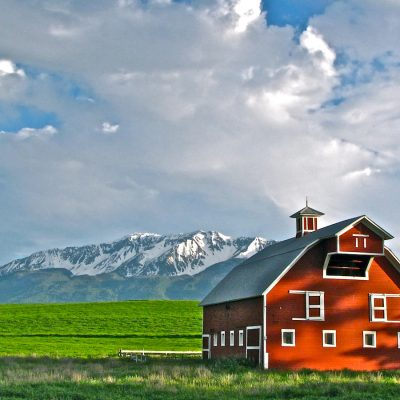 Red barn in a green field against snowy mountain backdrop with lighly clouded blue sky