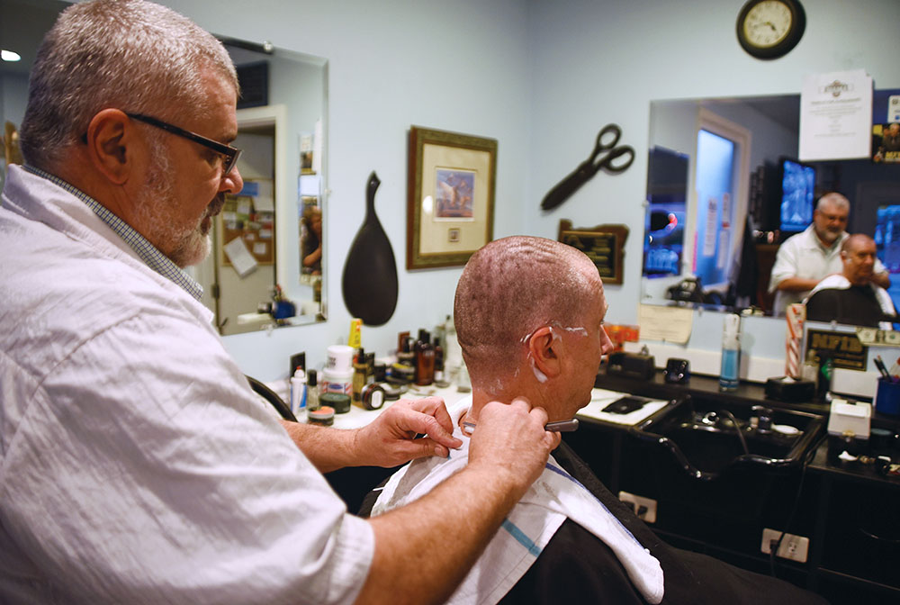 "Photo by Laura Hancock / Galen Miller, owner of Blue Mountain Barbers, finishes Craig Orton's cut with a straight shave. Orton, of La Grande, participates in the ""Haircuts for Scholarships"" project by designating $1 of his bill to go to the general scholarship fund at EOU."