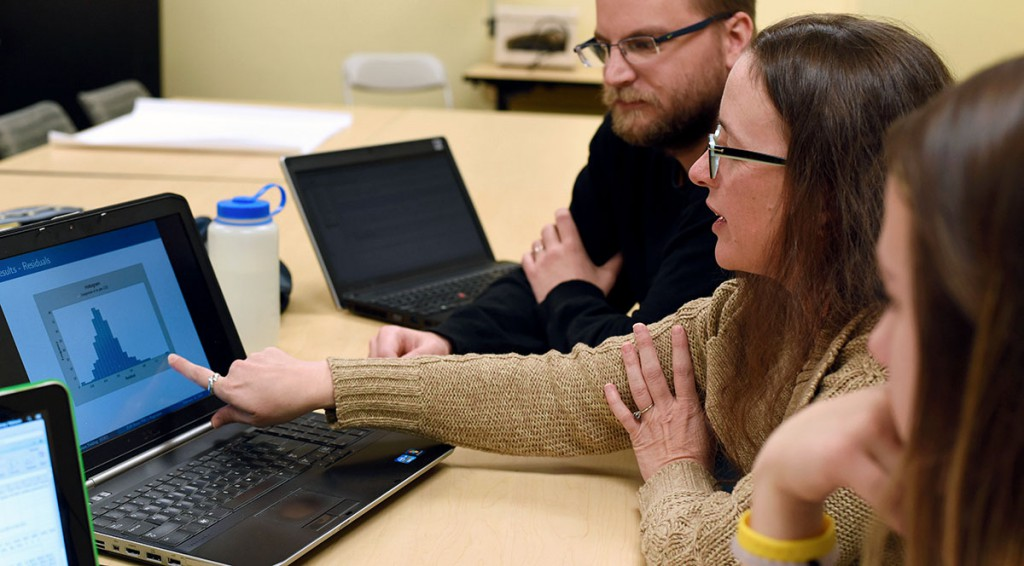 Professor Amy Yielding, center, reviews data with math students Travis Lowe and Sydney Nelson. Together they comprise the research team from EOU that partnered with the Oregon DEQ and NOAA to improve an air quality forecasting model being used in Burns to guide home heating and open burning practices.