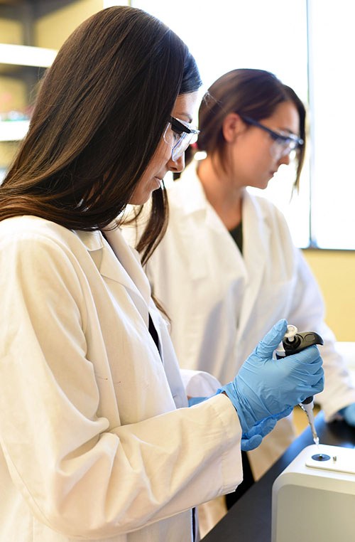 Gabby Rodriguez, front, and Anna Harris run samples using a NanoDrop. Rodriguez is a junior at La Grande High School and Harris just completed her bachelor's from Smith College. She sought out the research opportunity at EOU to prepare for grad school.