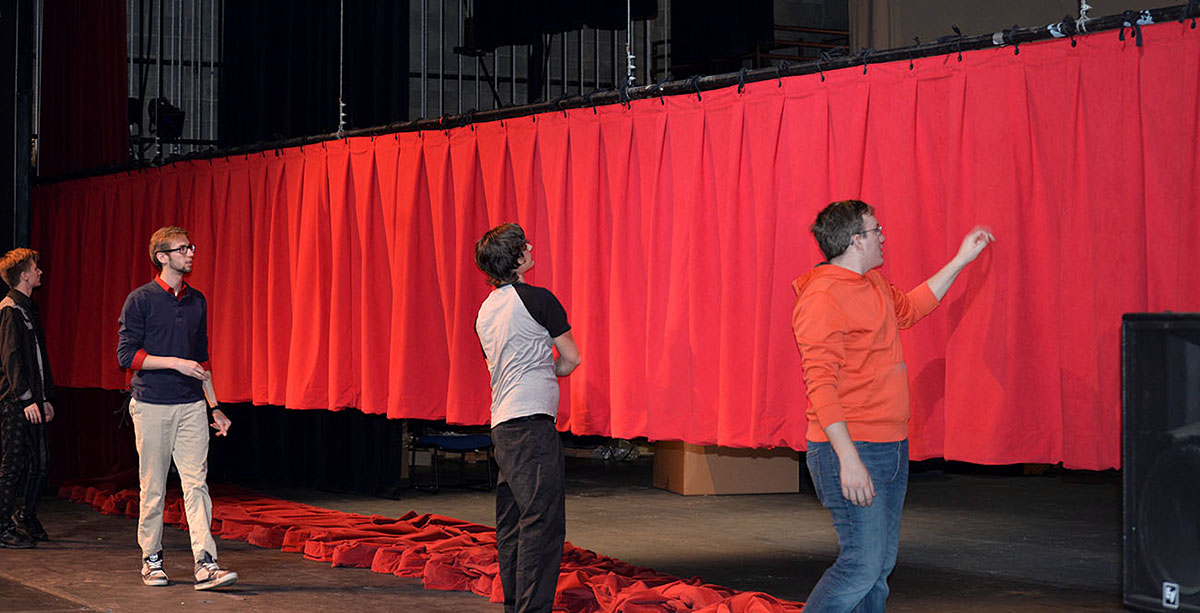EOU students, many majoring in theatre and music, stand back to admire the new velvet curtains installed last month. Through the vision of namesakes Glen and Jean McKenzie, the campus auditorium continues to be the main performance space for the eastern Oregon region.
