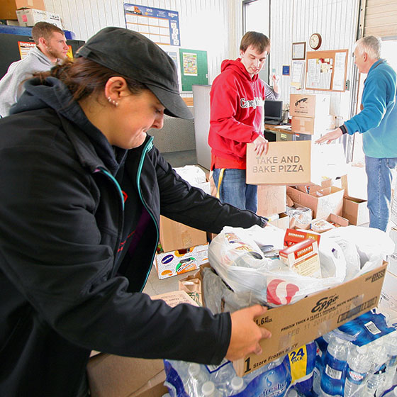 Jo Ball, foreground, stacks donations of non-perishable items in the loading dock at EOU in preparation for pick-up by local food banks. Ball is one of several sociology students who pitched in this year for the Governor's State Employees Food Drive, along with members of the Pre-Professional Health Club and university faculty and staff.