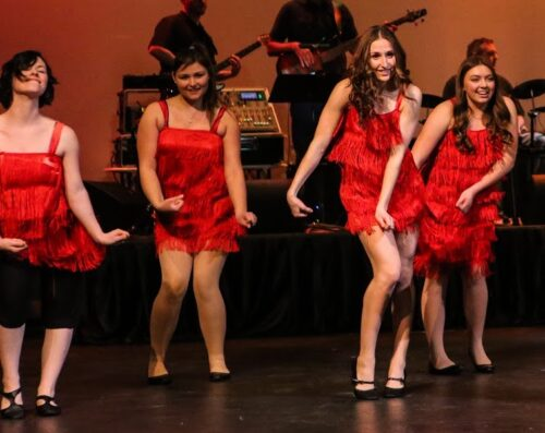 EOU students in Chamber Choir perform in red flapper dresses.
