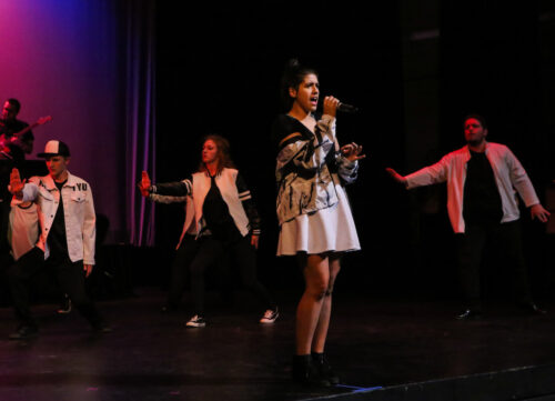 EOU music student sings on stage as other students dance