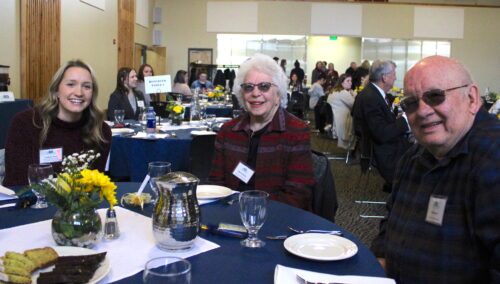 A student smiles alongside donors at Tea and Trumpets 2020