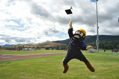 Monty mascot jumping in a graduation gown