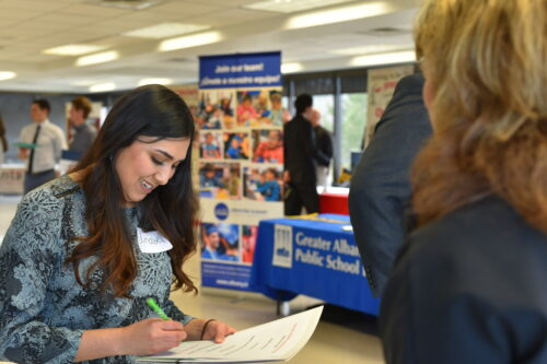 Woman signs a paper at a career fair