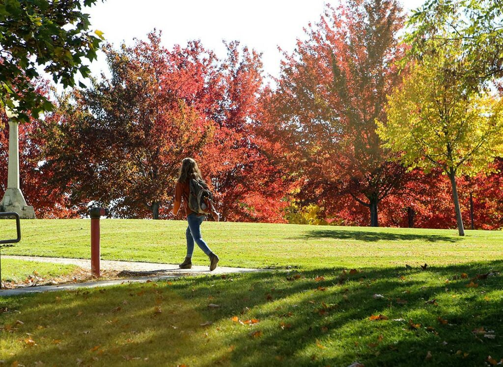 Picture of an EOU student walking on campus in fall
