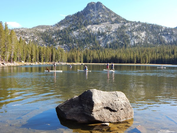 people paddleboarding on a mountain lake