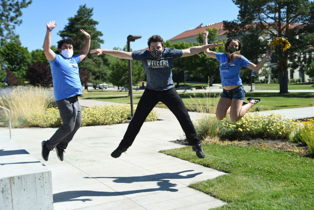 Three student wearing face coverings over their mouths are caught in mid-air as they jump up and celebrate week of welcome. They are on campus in front of Loso Hall.